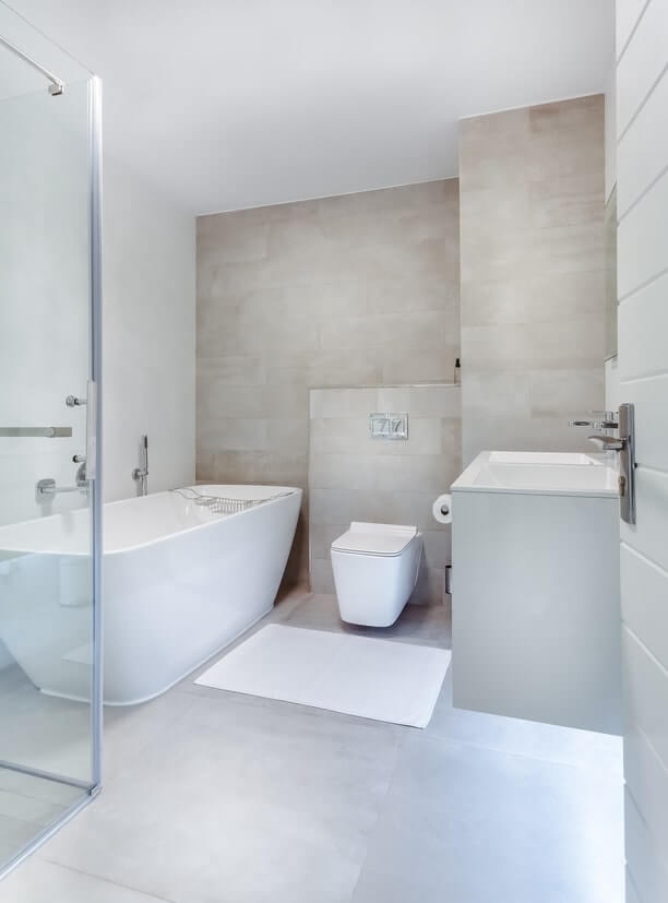 Modern bathroom with grey tiles on the floor and one wall. Free standing modern bath and toilet.