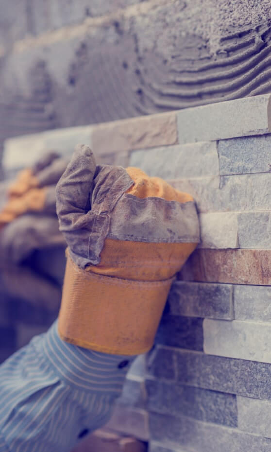 Brick tiles being used on a wall. The hands of the tiler press a tile against the half finished wall