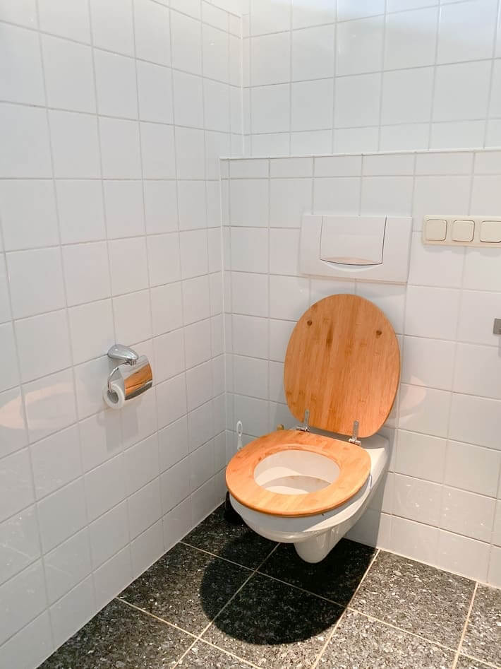 A toilet with a wooden seat. The walling are white tiles